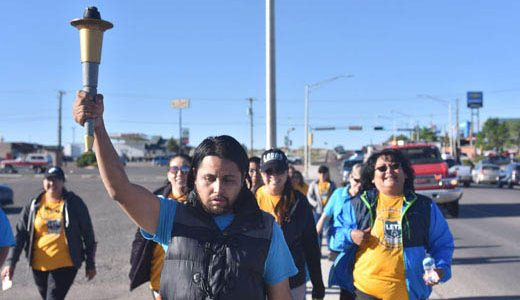Athlete Allen Leal holds up the torch during the first leg of the New Mexico Special Olympics Law Enforcement Torch Run on South Second Street in Gallup Monday morning.