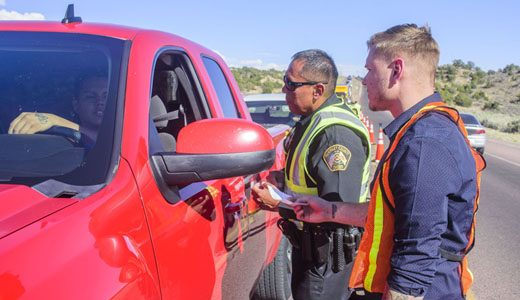 McKinley County SheriffÕs Deputy Monty Yazzie and Domnick Riffle, with the McKinley County DWI Program, talk to a motorist and hand out promotional items during a DWI Joint Task Force Checkpoint Tuesday afternoon on New Mexico Highway 602 near Park Avenue in Gallup.