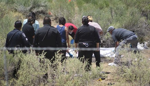 Gallup Police and medical investigtors examine a  body found in a field on U.S. Highway 491, Wednesday, July 11, in Gallup.