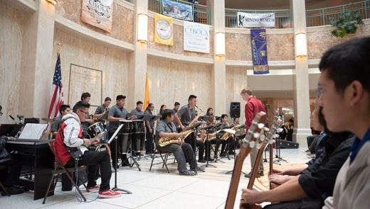 Students from Laguna-Acoma Jr/Sr High School and The Grants High School Jazz bands, led by Director William Griner, in red, open up with the Hawaii Five-O song in The New Mexico State Capitol Rotunda in Santa Fe Thursday.