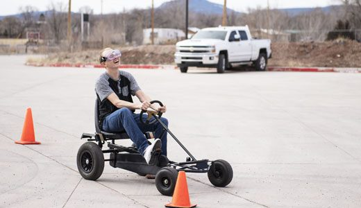 Dakota Shult Jr., 17, reacts to hitting a cone while wearing Fatal Vision Alcohol Impairment Simulation Goggles as he drives a pedal car in the parking lot of Grants High School as part of a drug awareness event Wednesday, Feb. 27.