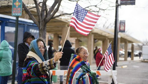 Dr. Carolene Whitman (left) and her mother  Elizabeth Whitman wave flags while watching the Veterans Day parade on Aztec Avenue,  Monday Nov. 12, in Gallup.