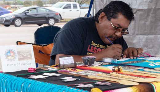Howard Lesariley, makes a few new book marks for a customer, during the Zuni Art Walk and Market on Saturday in Zuni Pueblo.